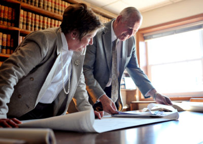 environmental portrait of lawyers looking at documents on conference table with library shelves in background