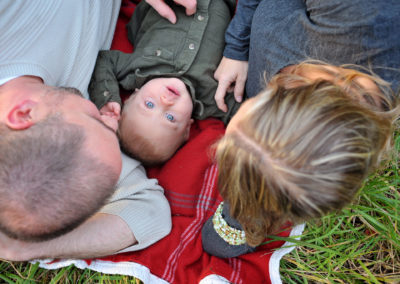 a couple laying on a blanket in the grass with a baby between them