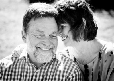 an older couple with faces close together laughing