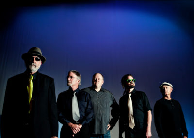 a 5-member band wearing all black and sunglasses with a blue background