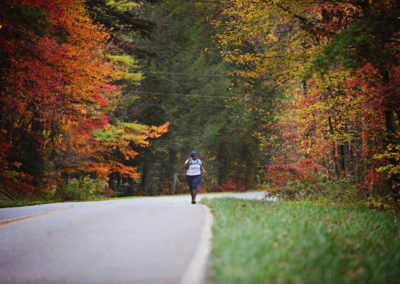 a woman running down a road in fall with bright autumn leaves on either side of her