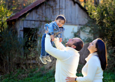 a father lifts a smiling toddler boy into the air as mom looks on from behind