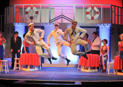 3 men dressed as sailors danc and jump in a community theater production