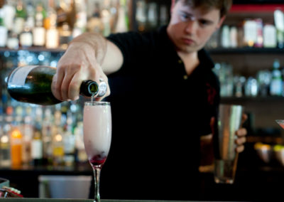 a bartender pouring a drink into a champagne glass