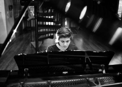 black and white photo through a piano lid of girl playing