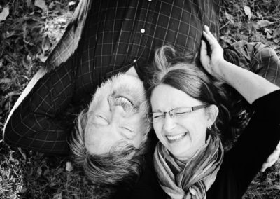 older couple laying together in the grass laughing