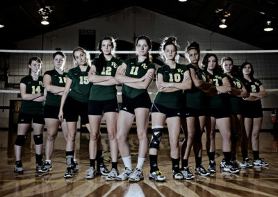volleyball team standing in an intimidating pose in a gym in front of volleyball net