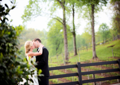 a bride and groom kissing in a vineyard with leaves in the foreground