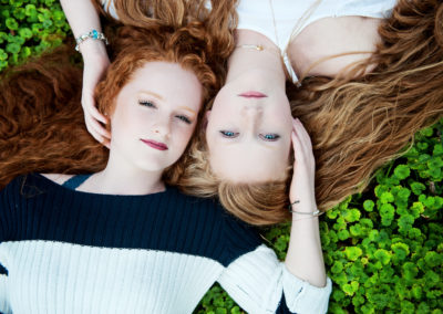 2 red-headed sisters in a clover field shot from above