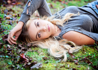 a teenage girl laying in the moss with her hand above her hand