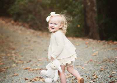 a toddler girl with a stuffed lamb in her hand laughs and runs away from the camera
