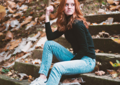 autumn portrait of a red headed girl sitting on stone steps in the woods