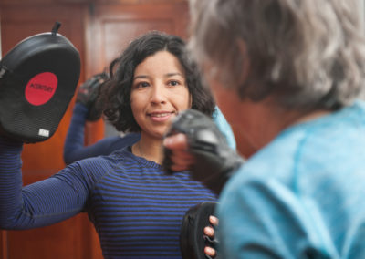 a trainer holds up a punching target for an elderly fitness client