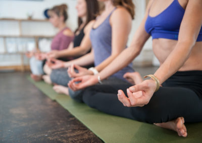 a line of women sitting cross-legged doing yoga, with forefinger and thumb circled together in the foreground