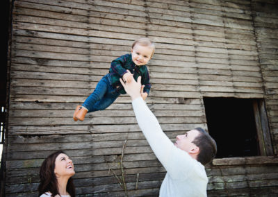 a father tosses a smiling baby into the air while mother looks on