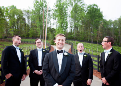 a groom in the foreground with 4 groomsmen looking shocked and laughing behind him