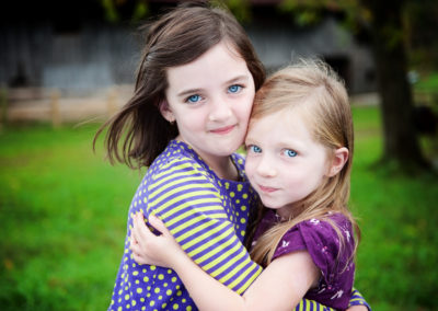 two young sisters hug each other