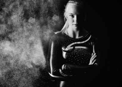 black and white image of a fierce gymnast with smoke behind her