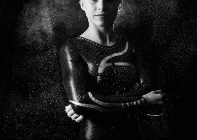 black and white image of a female gymnast with smoke behind her