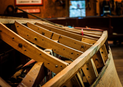 A wooden chris craft boat ribs in the middle of restoration
