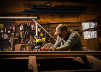 A man sanding down the wooden frame of a Chris Craft boat in the process of restoration