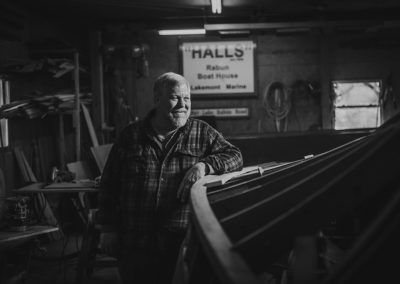 Black and white image of a man standing next to a wooden boat frame in the process of restoration