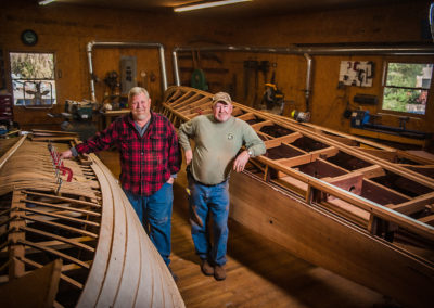 two men in their wood shop stand next to wooden boats in the process of restoration