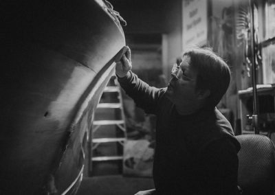 A black and white image of a man backlit from a window as he hand sands a wooden boat in the process of restoration