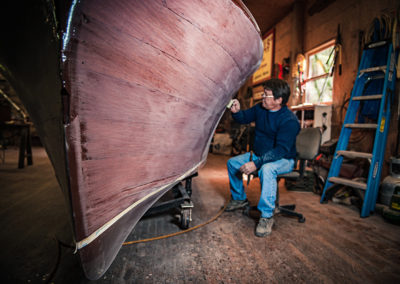 a wide angle image of a boat prow with a man in the background sanding it