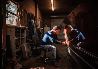 A man is backlit from a window as he hand sands a Chris Craft wooden boat in the process of restoration