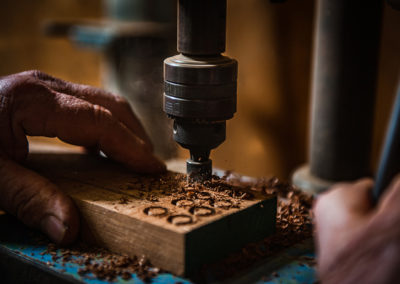 man using a drill press to make wooden plugs to a boat restoration
