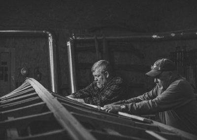 black and white image of two men working together to restore a vintage wood boat