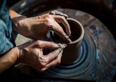 a potters hands shaping a vessel on the wheel