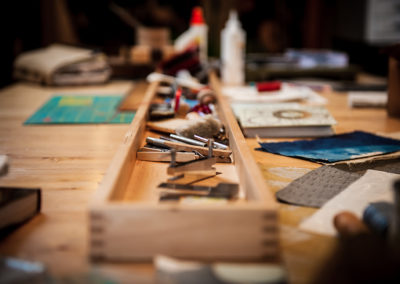 small collection of book binding tools in a long wooden box on a table