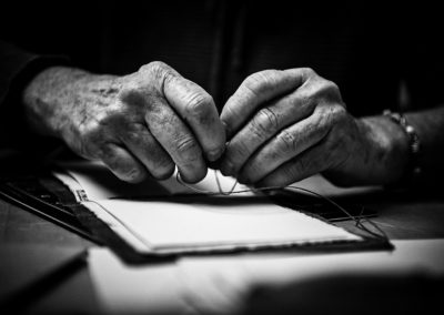 black and white image of older hands sewing a book together in book binding process