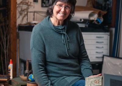 older female artisan holding books for book binding