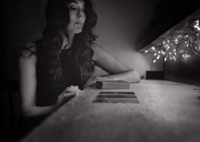 black and white image of woman dealing tarot cards during a reading