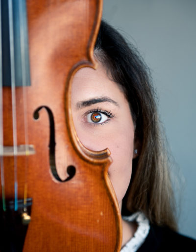 woman with violin up to her brown eye