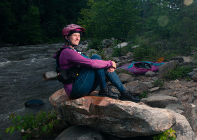 Female kayaker sitting on large rock on chattooga river