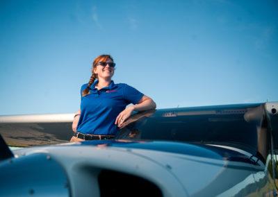 female pilot leaning against grounded plane