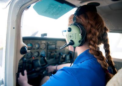 female pilot hand on cockpit control