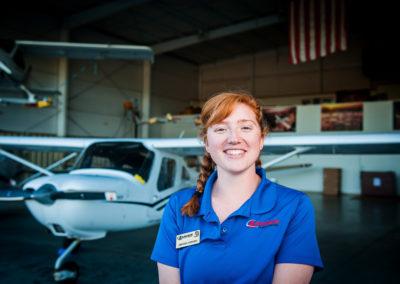female pilot in airplane hanger