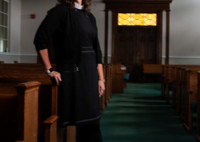 female clergy leaning against pew