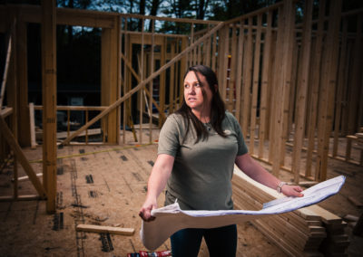 Female Contractor at job site looking at architectural drawings