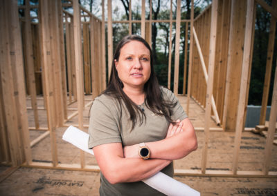 Female Contractor at job site with architectural drawings under her arm