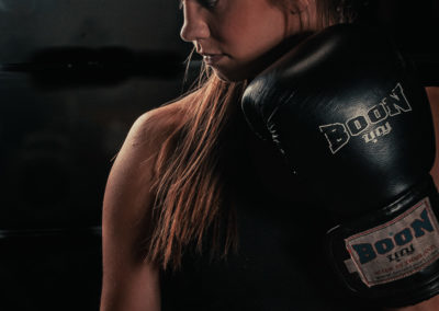 female mma fighter with boxing glove in front of face