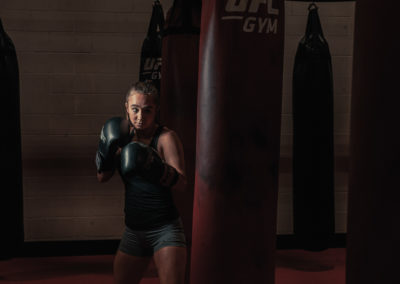 female MMA fighter with gloves and punching bag