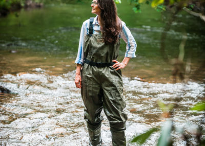 female environmentalist standing in river with waders on