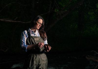 female environmentalist examining rocks in river